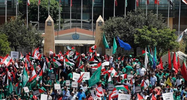 Palestinians hold Lebanese, Palestinian and Hamas flags during a demonstration against a U.S.-sponsored Middle East economic workshop in Bahrain, in front of the United Nations headquarters in Beirut, Lebanon, June 25, 2019.