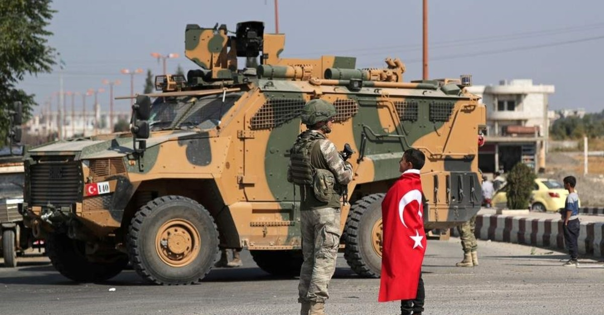 A boy wearing a Turkish flag stands next to a Turkish soldier in the town of Tal Abyad, Syria Oct. 23, 2019 (Reuters Photo)
