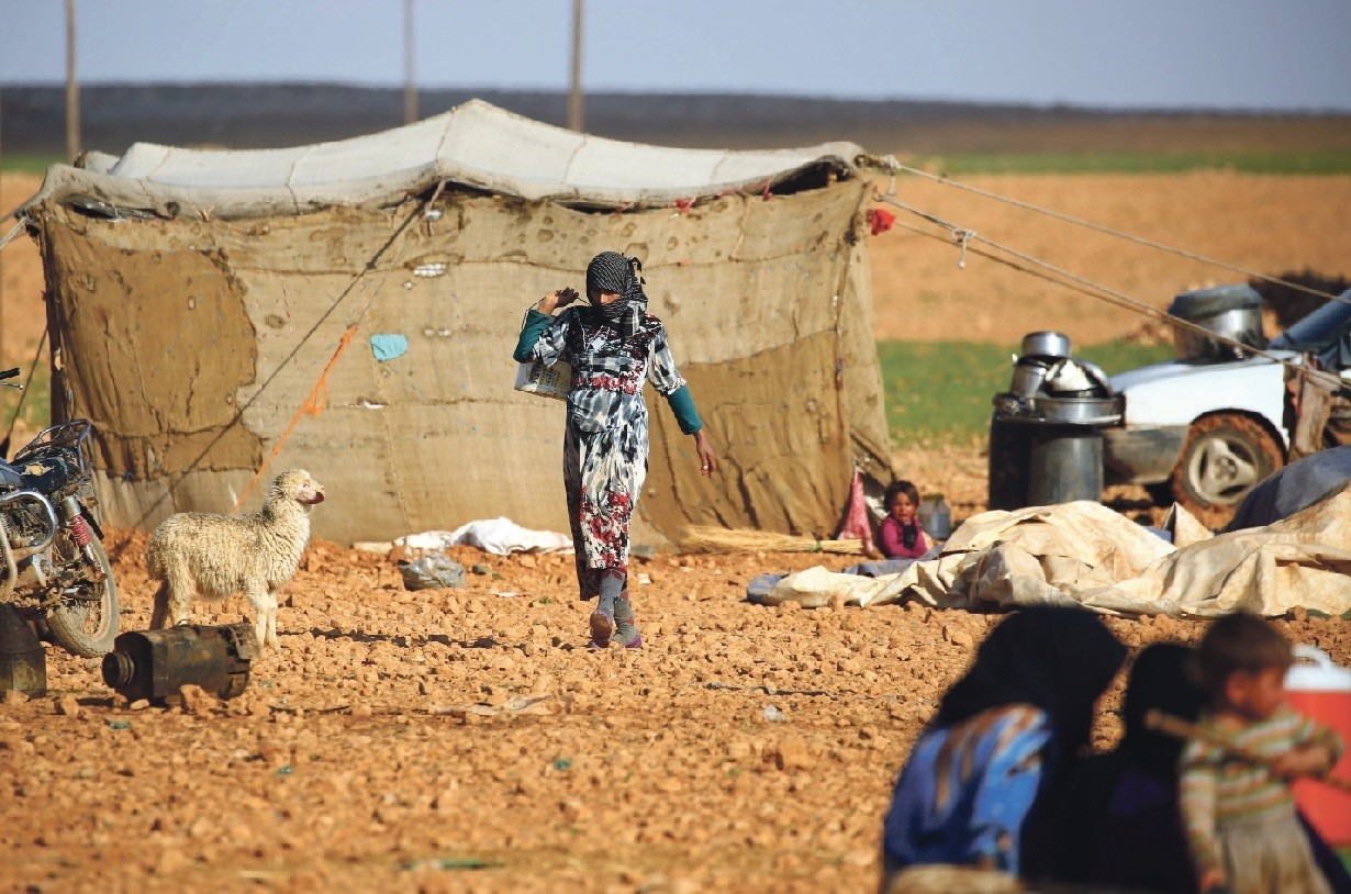 A displaced Syrian woman walking at a makeshift camp in the village of Jab al-Tur, also known as Ukuz Quy, on the southern outskirts of Manbij, March 7.