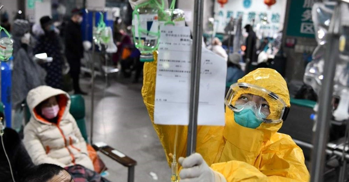 A medical worker in protective suit adjusts a drip bag for a patient at a hospital, following an outbreak of the new coronavirus in Wuhan, Feb. 3, 2020. (Reuters Photo)
