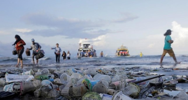 People walk down a beach polluted by plastic waste.