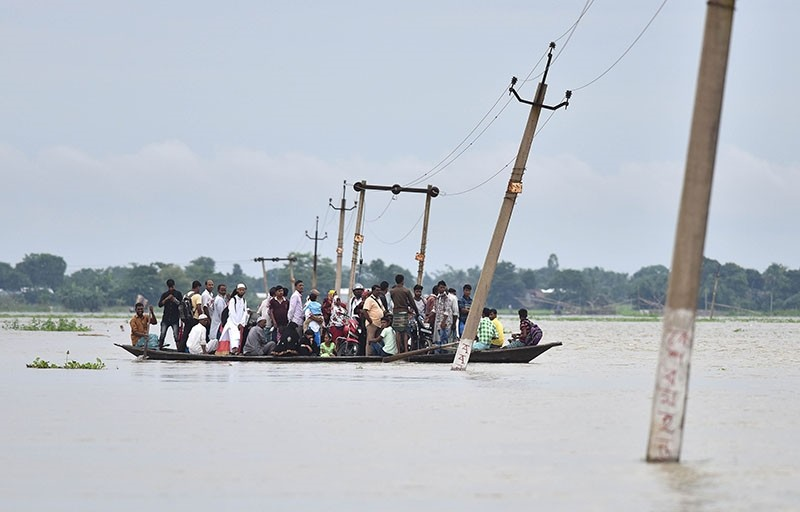 Indian villagers travel by boat through floodwaters in Balimukh Ashigarh village in Morigoan district, in India northeastern state of Assam, on July 4, 2017 (AFP Photo)