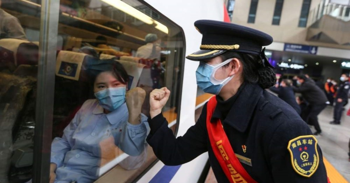 Train attendant gestures to medical staff leaving for Wuhan in Nanchang, central Jiangxi province, China. (STR via AFP)