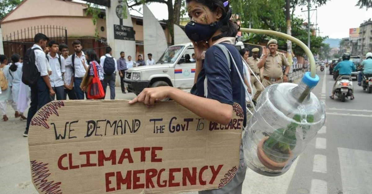 A youth connected to a jug with a plant inside holds a placard at a protest calling for the Indian government to declare a climate emergency in Guwahati on Nov. 8, 2019. (AFP)