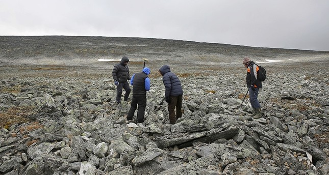 In this photo taken on Sept. 4, 2017, archeologists and the two hunters who found an ancient Viking sword, search the site where it was discovered on a mountain top (AP Photo)