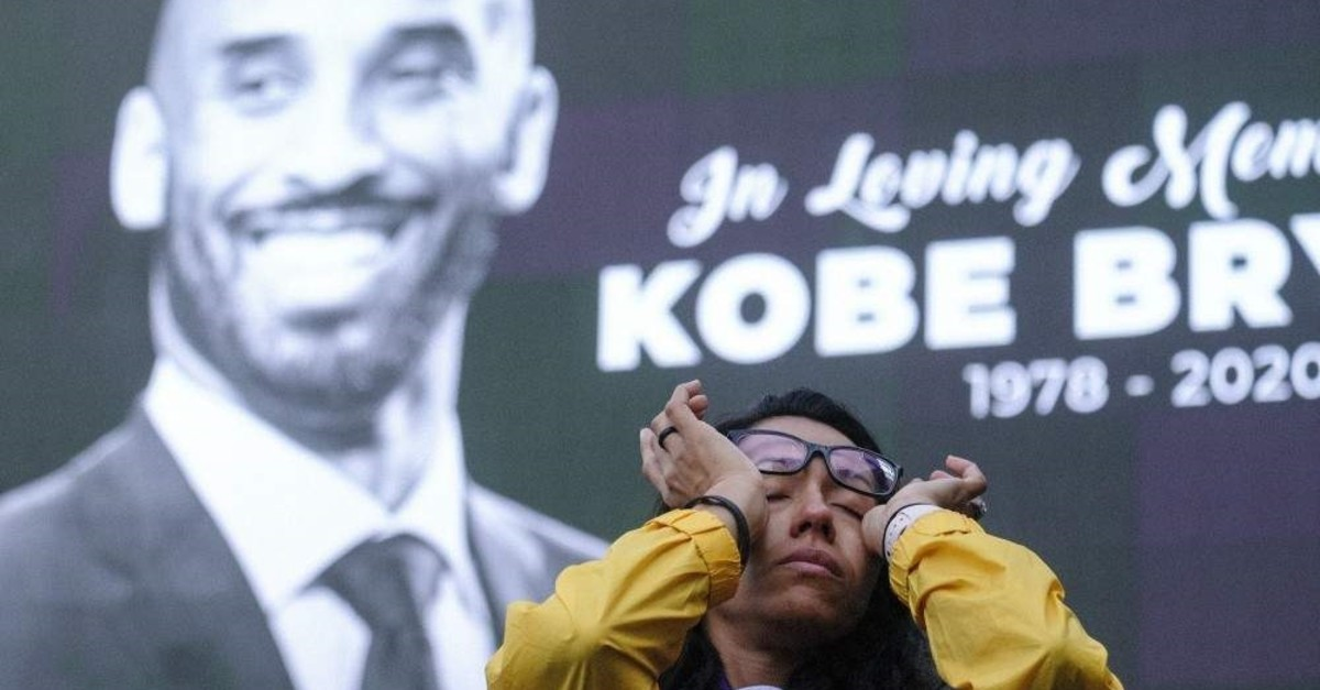 A woman wipes her eyes in front of a screen with the late Kobe Bryant at a memorial near Staples Center, Jan. 27, 2020. (AP Photo)