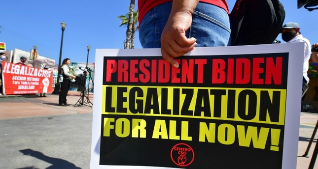 متظاهر يحمل لافتة تطلب من بايدن تسوية أوضاع ملايين اللاجئين غير النظاميين في الولايات المتحدة الفرنسية