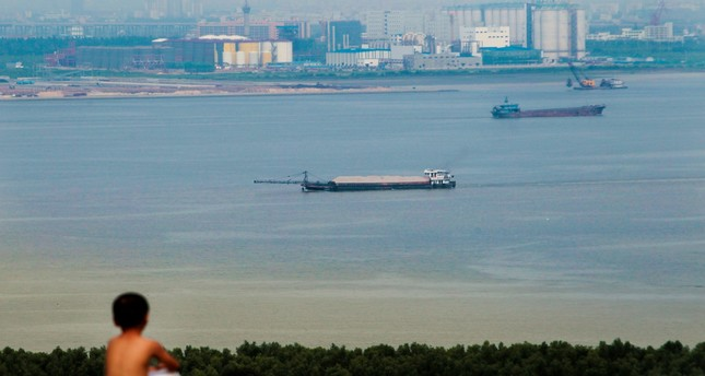 A boy looks at cargo ships passing along the Pearl River in Guangzhou, Guangdong province, Aug. 6, 2014.