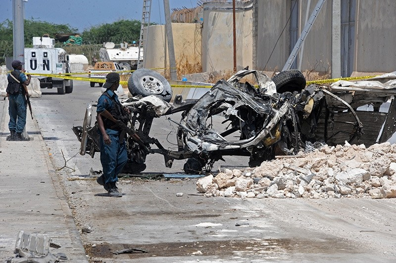 omali soldiers pass near the wreckage of a car bomb outside the UN's office in Mogadishu on July 26, 2016. (AFP Photo)