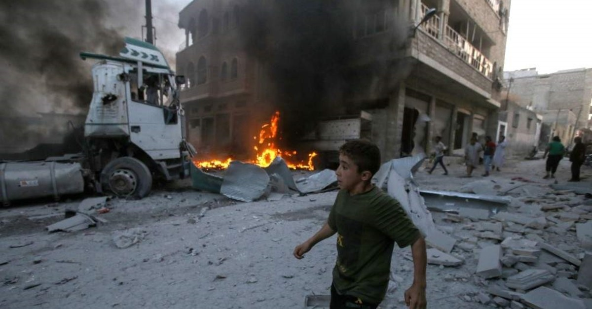 A young boy runs past a fire started in a building following a reported airstrike by Syrian regime forces in the town of Maaret al-Numan in Syria's northwestern Idlib province on Aug. 28, 2019. (AFP Photo)