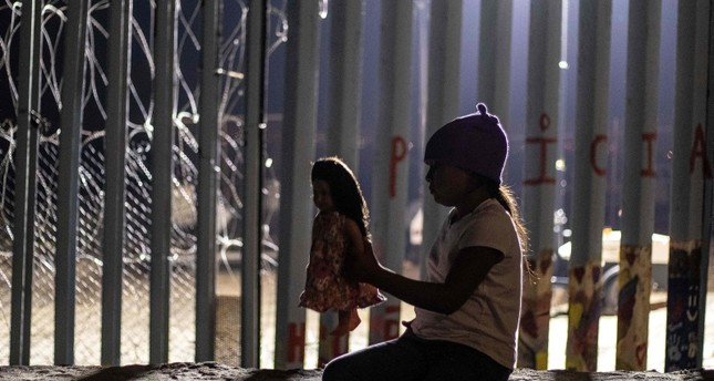 A girl from Guatemala, part of the Central American migrant caravan, plays with a doll near the US-Mexico border fence in Playas de Tijuana, Baja California state, Mexico on December 9, 2018. (AFP Photo)