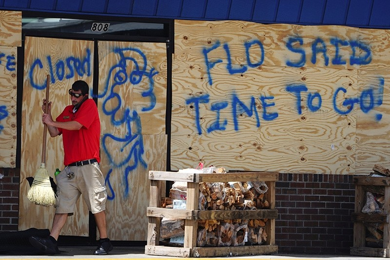A man sweeps the entrance of a boarded up store before Hurricane Florence comes ashore in Carolina Beach, North Carolina, U.S., Sept. 12, 2018. (Reuters Photo)