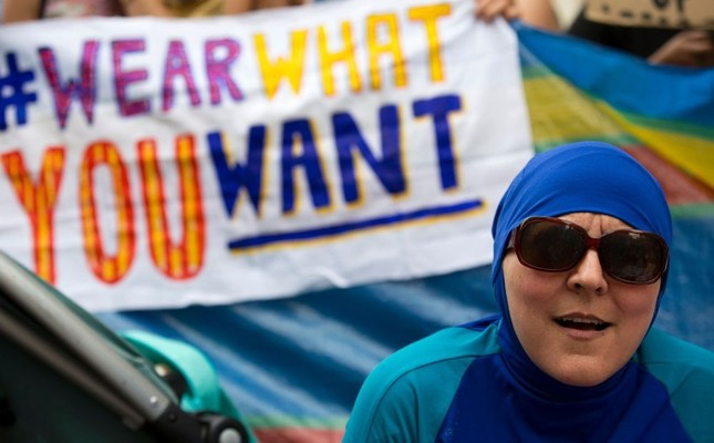 Woman wearing a burkini joins a protest outside the French Embassy in London.