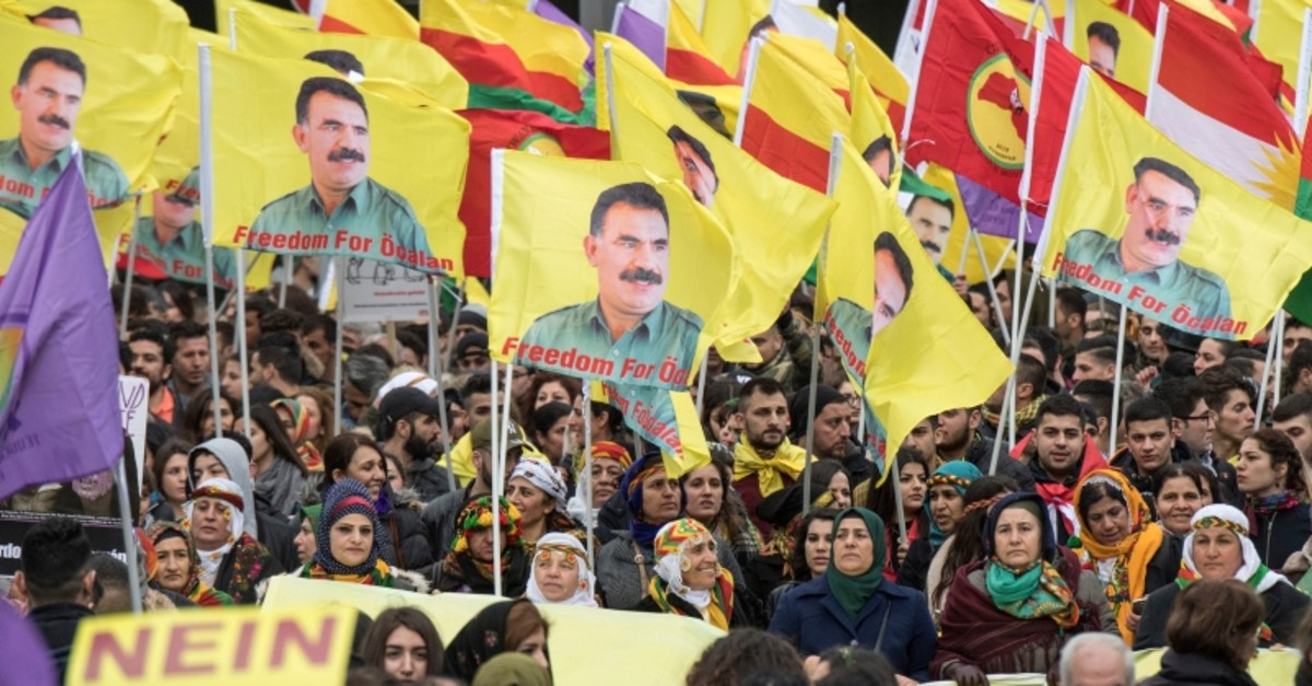 Terror symphatizers living in Germany gather and wave flags with portraits of arrested PKK leader Abdullah Ocalan in Frankfurt, Germany, Saturday, March 18, 2017. (AP Photo)