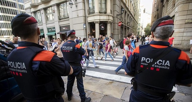 Agents from the Mossos d'Esquadra, Catalonian regional police, on guard in the streets of Barcelona, Spain (EPA Photo)