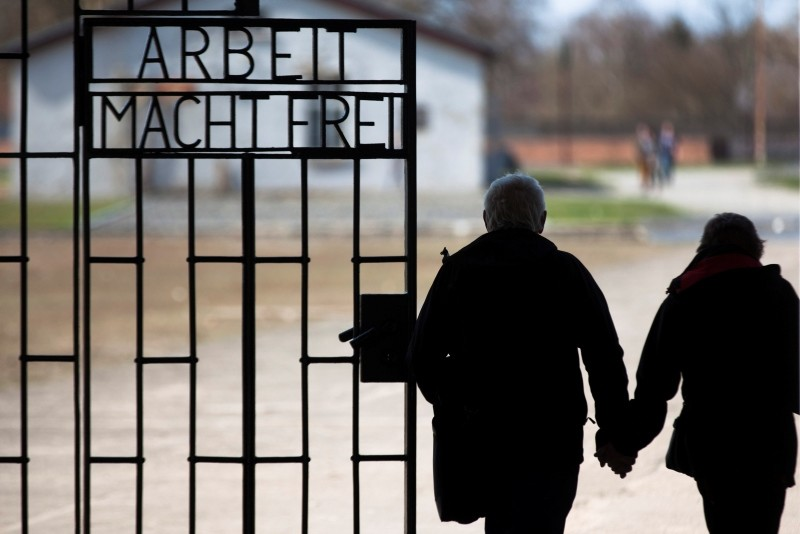 In this Jan. 27, 2012, file photo, a couple walks past the slogan 'Arbeit Macht Frei' (Work Sets You Free) at the main entrance of the Sachsenhausen Nazi concentration camp on the international Holocaust remembrance day in Oranienburg. (AP Photo)