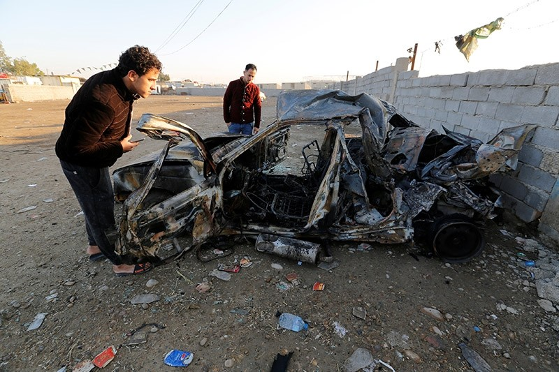 Men look at the wreckage of a burnt car after a suicide bomber detonated a pick-up truck on Wednesday in Sadr City, a heavily populated poor Shi'ite suburb of Baghdad, Iraq, February 16, 2017. (Reuters Photo)