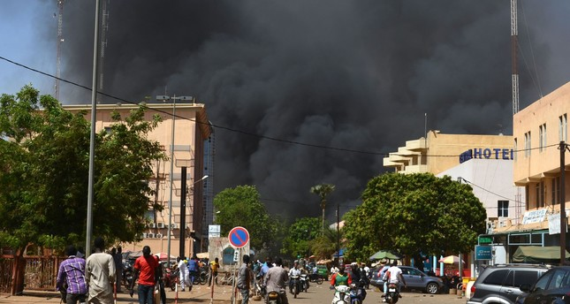 People watch as black smoke rises as the capital of Burkina Faso came under multiple attacks on March 2, 2018, targeting the French embassy, the French cultural centre and the country's military headquarters. (AFP Photo)