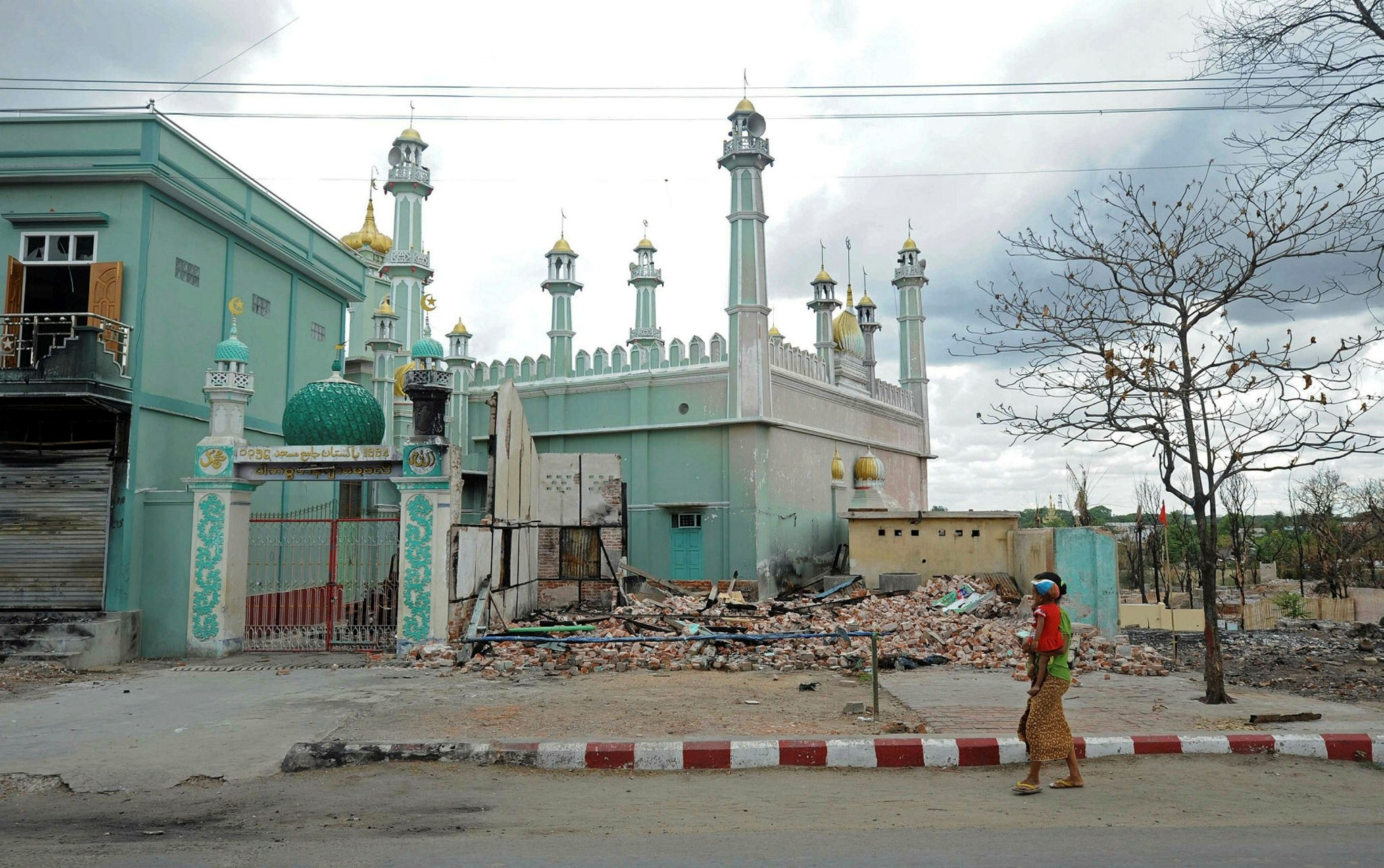 This picture taken on June 4, 2013 shows a woman carrying a child past a damaged mosque in riot-hit Meiktila, central Myanmar. (AFP Photo)
