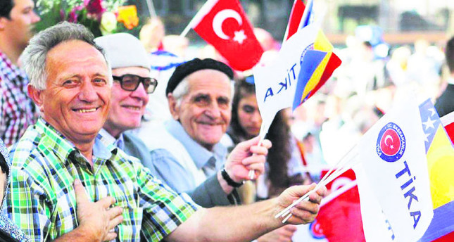 People wave Turkish and Bosnian flags at an opening ceremony for a project by the Turkish Cooperation and Coordination Agency (TİKA) in Bosnia.