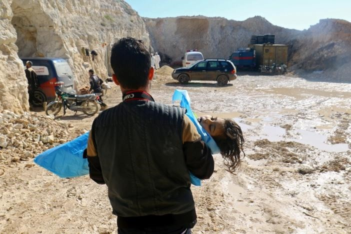 A man carries the body of a dead child, after what rescue workers described as a suspected gas attack in the town of Khan Sheikhoun in moderate opposition-held Idlib, Syria April 4, 2017. (Reuters Photo)