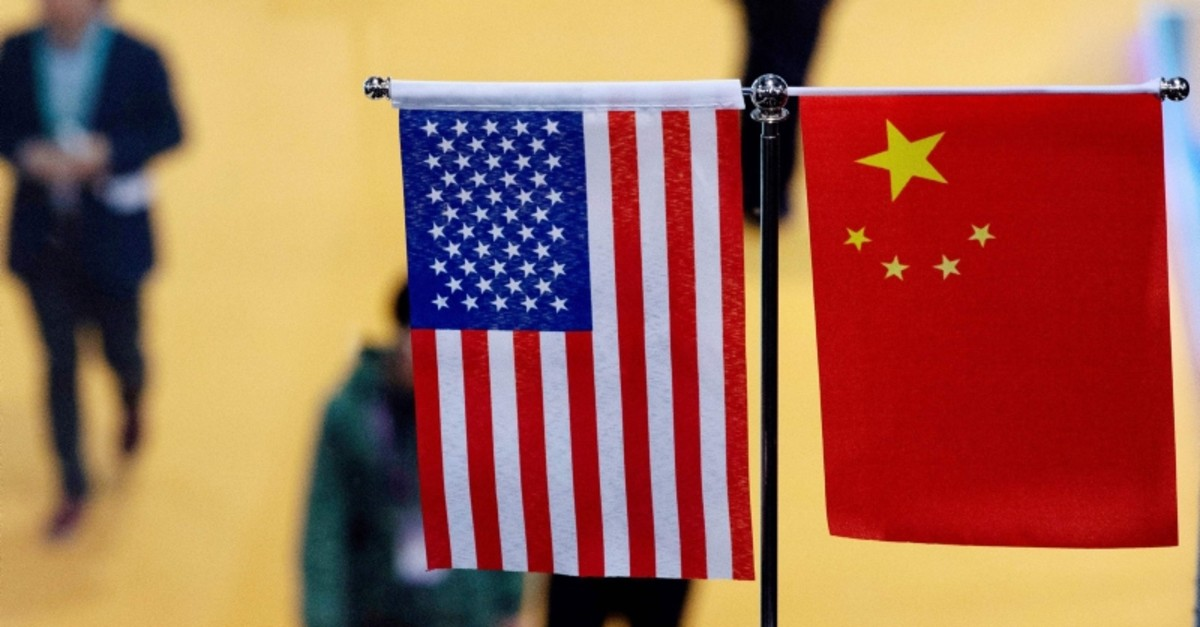 This file picture taken on November 6, 2018 shows a Chinese and US flag at a booth during the first China International Import Expo  in Shanghai. (AFP Photo)
