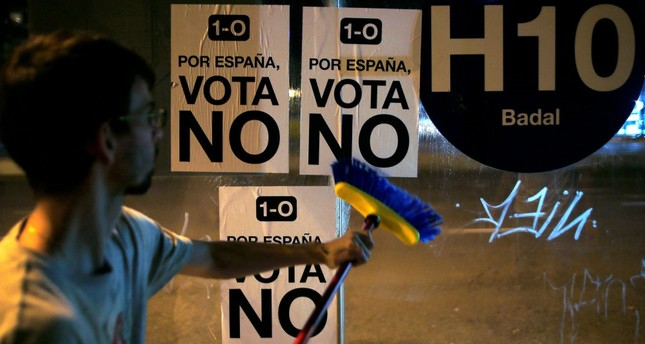 A youth puts up posters reading, 1- October. For Spain, vote no, in reference to voting in the banned Oct. 1 independence referendum, at a bus stop in Barcelona, Spain, early Sept. 23.