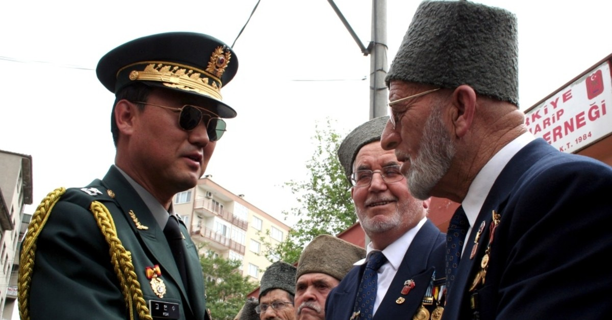 Hyun Soo Koh, South Korean military attache in Ankara, shakes hands with two Turkish Korean War veterans during a medal ceremony for veterans in the northwestern city of Bursa, April 22, 2008.