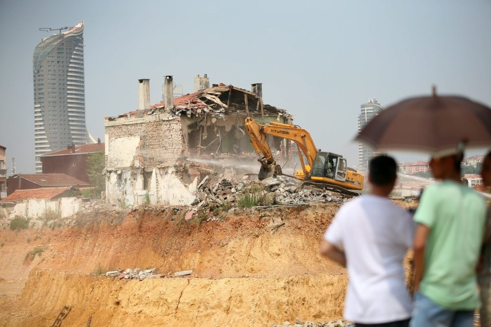 People watch as a bulldozer demolishes a house in Fikirtepe, the Istanbul district where old buildings are being replaced with modern residences as part of urban transformation project.