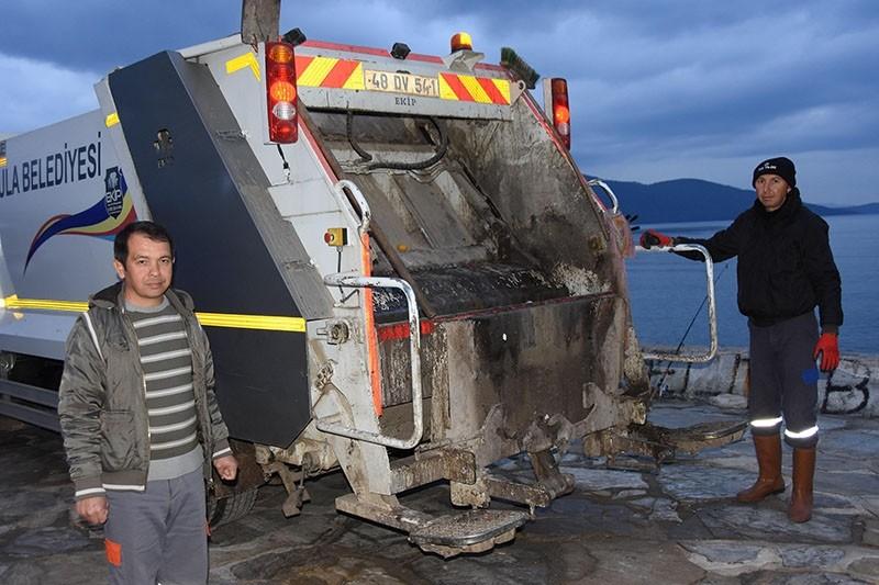 Feridun u00d6zsoy (L), village headman of Muu011fla's Akyaka neighborhood, works an evening shift as garbage truck driver. (DHA Photo)
