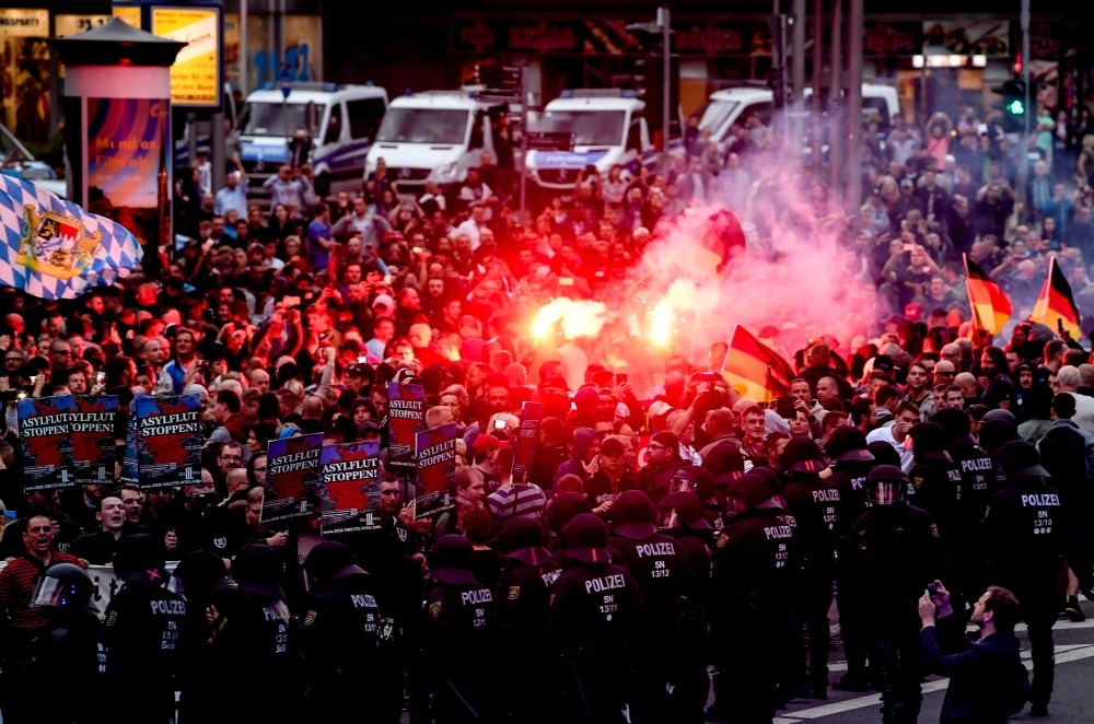 Right wing protesters light flares while facing police, Chemnitz, Aug. 27.