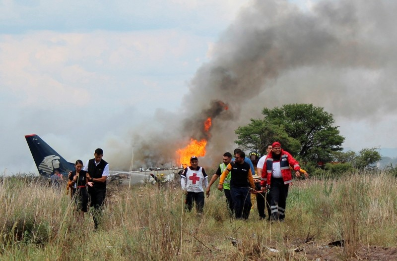 In this July 31, 2018 photo released by Red Cross Durango office, rescue workers carry an injured person as airline workers walk away from the site where an Aeromexico airliner crashed near the airport in Durango, Mexico. (AP Photo)