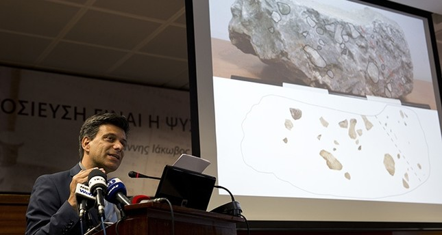 Greek archaeologist Christofilis Maggidis speaks as a photograph of a stone he believes belonged to the lost royal throne in the ancient palace of Mycenae, in Athens, on Tuesday, June 14, 2016. (AP Photo)