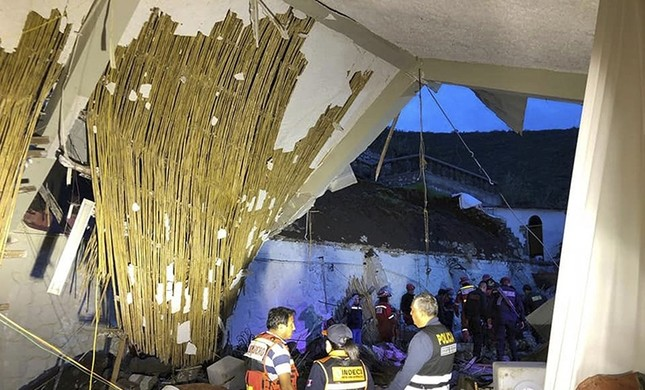 In this photo provide by Abancay police, officers and firefighters stand by a collapsed area of the Alhambra hotel in Abancay, Peru, Sunday, Jan. 27, 2019. (AP Photo)
