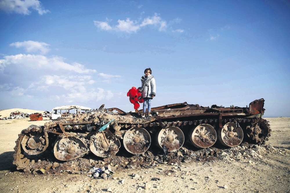 A Syrian girl poses on a destroyed tank with her stuffed bear near the village of Yazi Bagh, Aleppo, Feb. 19, 2019.