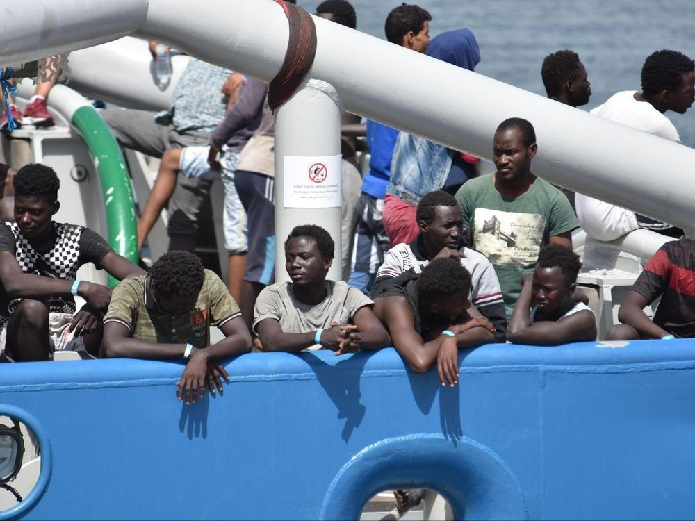 Migrants stand on the deck of the Swedish Navy ship Bkv 002, as they wait to disembark in the Sicilian harbor of Catania, Italy, July 1.