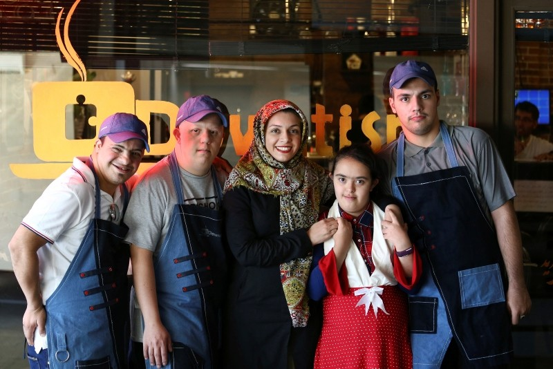 In this Monday, Aug. 6, 2018, photo, Aylin Agahi founder of Downtism Cafe and a musician, center, poses for a photo with some of her staff, in Tehran, Iran. (AP Photo)