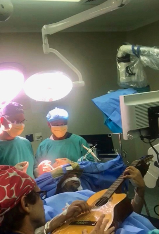 In this photo supplied by the Department of Neurosurgery, Inkosi Albert Luthuli Central Hospital on Saturday, Dec. 22, 2018, taken earlier this month during surgery South African musician, Musa Manzini, plays a guitar during brain surgery. (AP Photo)