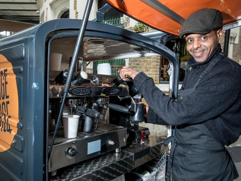 Abobaker serves coffee from a motorized coffee cart for the social enterprise Change Please, after 12 years of homelessness.