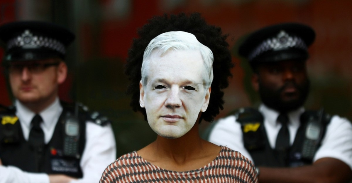 Police watch an Assange supporter wearing a mask and protesting at Westminster Magistrates Court in London, Friday, June 14, 2019. (REUTERS Photo)