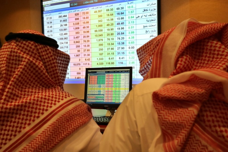 Saudi traders follow shares on screen at the stock market trading room in Riyadh, Saudi Arabia, 15 October 2018. (EPA Photo)