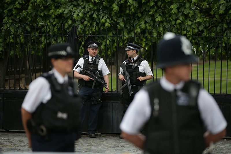 Armed British Police officers stand on duty outside of the Houses of Parliament in Westminster, central London on May 23, 2017 (AFP Photo)