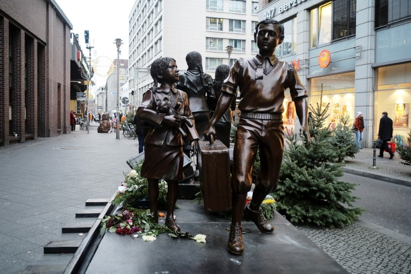 People pass a commemorative memorial statue to perpetuating the memory of the 'Kindertransport' (children transport) near Friedrichstrasse train station in central in Berlin, Germany, Monday, Dec. 17, 2018. (AP Photo)