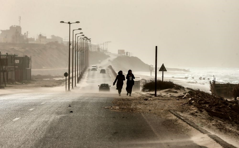 Two women walk along the sea front as heavy winds blow dust and sand across a main road, Gaza city, Jan. 6.