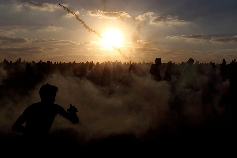 Palestinians run from tear gas during a protest calling for lifting the Israeli blockade on Gaza and demanding the right to return to their homeland, at the Israel-Gaza border fence, in the southern Gaza Strip Sept. 21, 2018. (Reuters Photo)