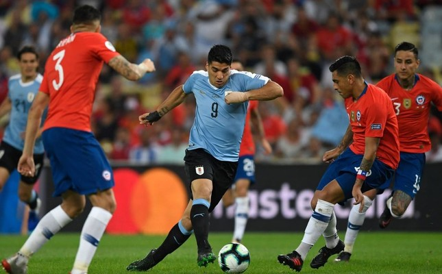 Uruguay's Luis Suarez (C) is marked by Chile's Gonzalo Jara (R) during the match in Rio de Janeiro, Brazil, June 24, 2019.