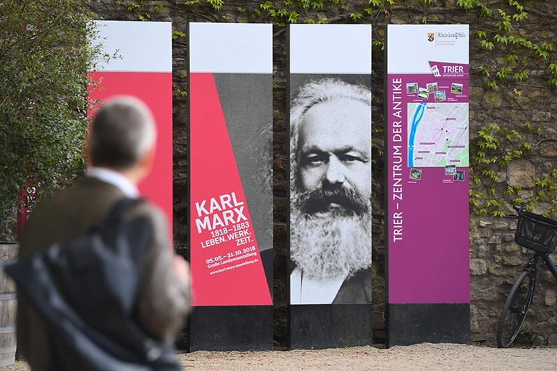 A man walks past boards displayed in Trier, southwestern Germany, as part of the celebrations marking 200 years of the birth of German philosopher Karl Marx on May 3, 2018. (AFP Photo)