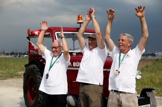 Swiss fans Josef Wyer, Beat Studer and Werner Zimmermann celebrate after driving an old-time tractor from home to Kaliningrad stadium to watch their team playing against Serbia, in Kaliningrad, Russia. (Reuters Photo)
