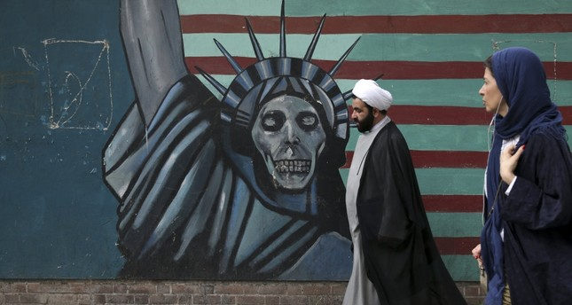 A cleric and a woman walk past an anti-U.S. mural painted on the wall of the former U.S. Embassy in Tehran.