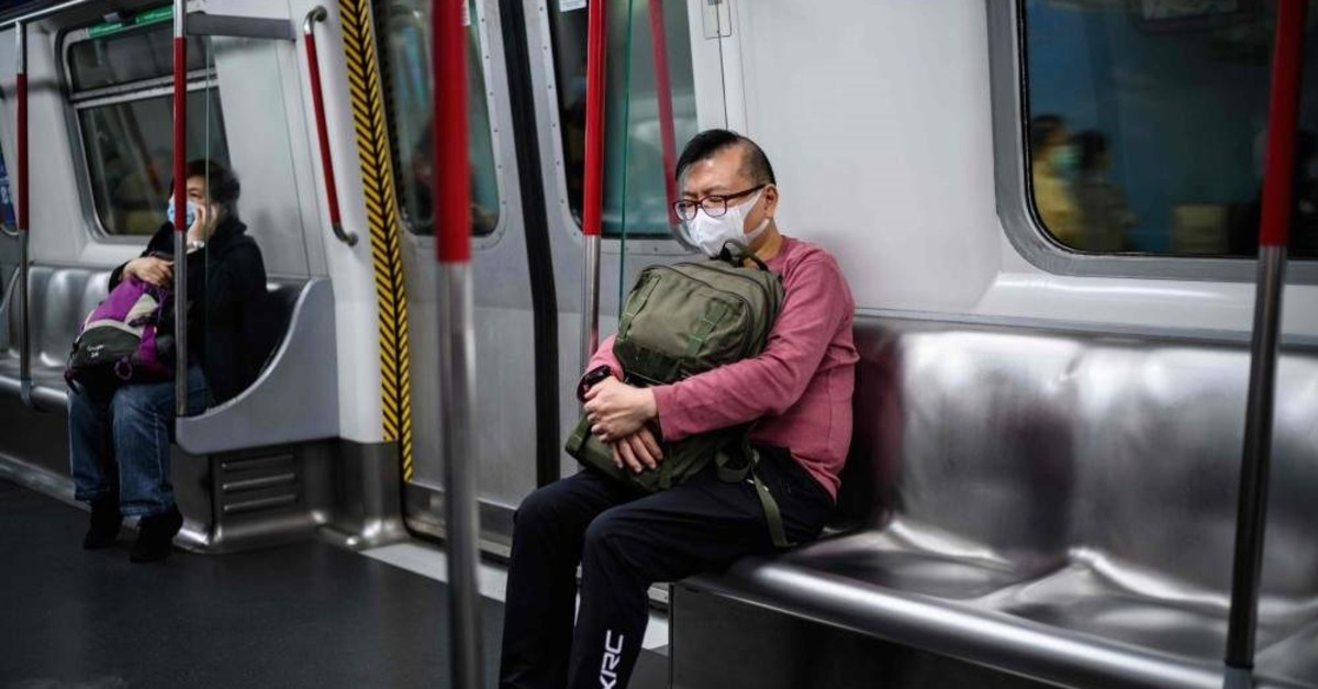 Commuters wear face masks as they travel on an MTR underground metro train, Hong Kong, Feb. 3, 2020. (AFP Photo)
